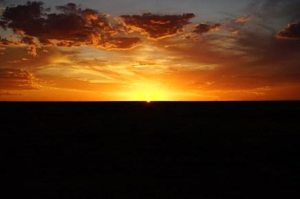 This is outback of Australia. Sun, horizon, crazy sky, full of drama