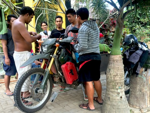 """After the bad accident in Flores, i somehow manage to ride to next island. While i was on the ferry, this man approached and asked me what happened. he saw me limping. I told him the story. Then he wanted to see the bike. After inspecting it, he said """" i like to fix your bike and my cousin is a Chiro, he can fix your back"""". i'm like...hang on a sec..is this some sort of scam? then, i trusted him after spending some time on the ferry (you have lots). His name is Stephanus Paulus. He was like """"god send"""". He looked after me for 3 days, fed yummy food, put a new front rack, handle bars bent removed. many other small jobs. Totally dedicated and exceptional skill and the whole family hospitality. Its just hard to believe in a nutshell!. there he's (shirtless) fixing all day, while his cousins and family keeping us company."""