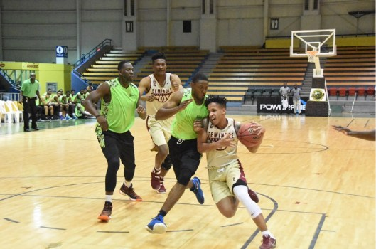 Florida State University's CJ Walker (right) powers ahead of Tyrone Lattibeaudiere of the Jamaica select team during their preseason basketball game at the National Indoor Sports Centre on Monday Night.