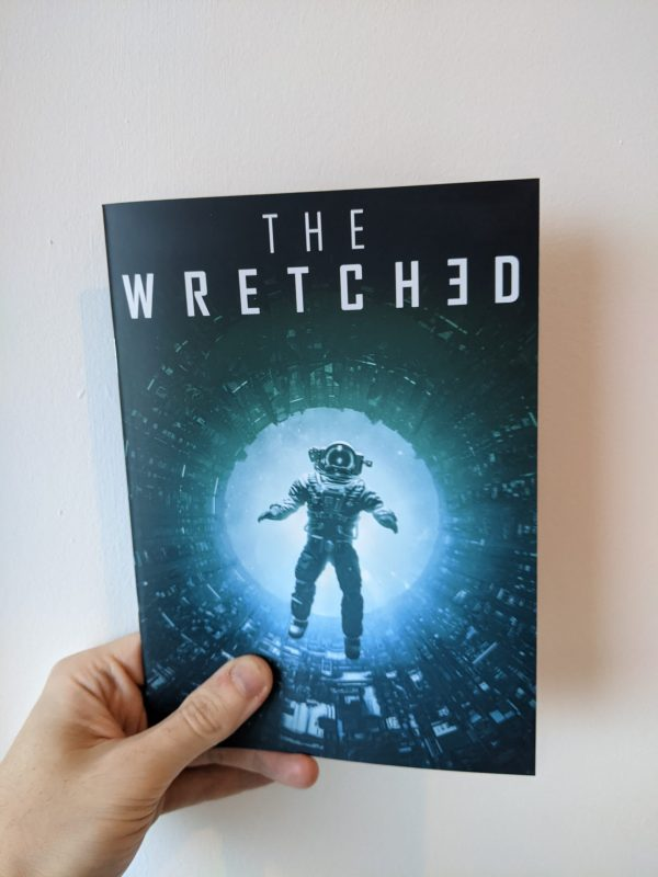 """A hand holds an A5 zine against a white background. The title on the zine reads """"The Wretched"""". On the cover, a silhouette of an astronaut falls backwards into a glowing green and blue void in the middle of a maze of industrial pipework."""