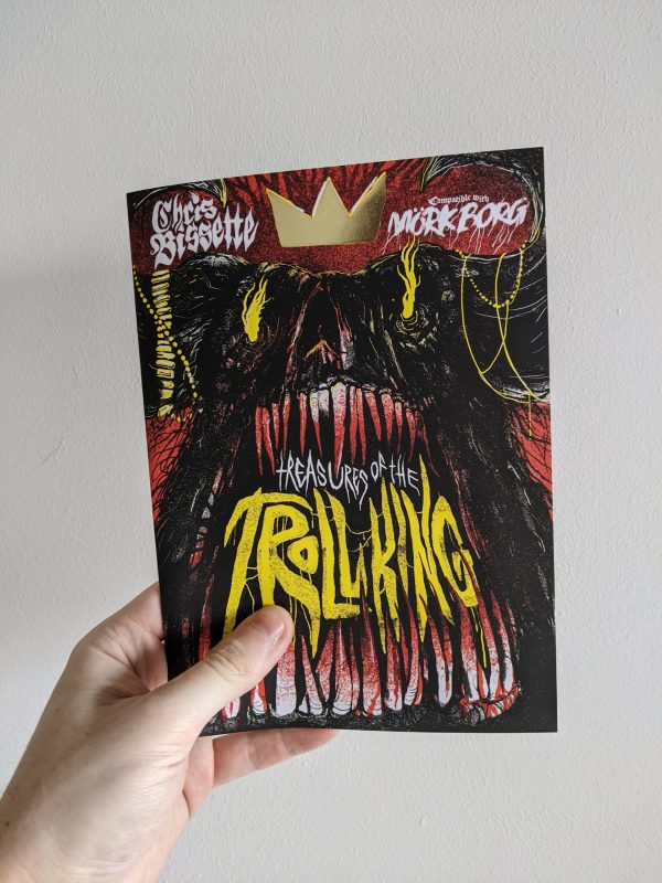"""An A5 zine held against a plain white background. The cover shows a dark dreature with an abundance of teeth, dripping in blood. In the space between the teeth yellow text reads """"Treasures Of The Troll King"""". The creature wears a crown that is printed in gold foil."""