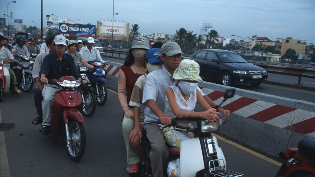 Whole families ride on motorcycles in a busy street_Vietnam