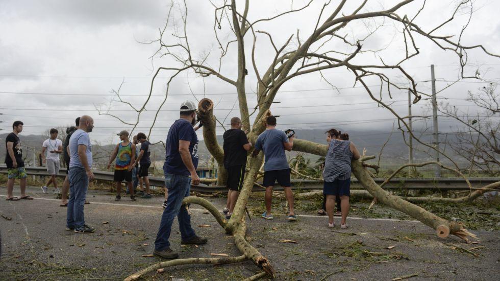 Huracán María golpea Turcas y Caicos, Puerto Rico y Dominicana - Vecinos ayudan a retirar escombros tras el paso del huracán María en Yabucoa, Puerto Rico, 21 de septiembre de 2017. La tormenta se acercaba a las islas Turcos y Caicos el viernes 22 de septiembre de 2017. (AP Foto/Carlos Giusti)