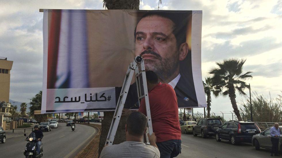 Partido libanés exige regreso de primer ministro tras renuncia - Trabajadores colocan un cartel del primer ministro saliente Saad Hariri con una inscripción en árabe que dice