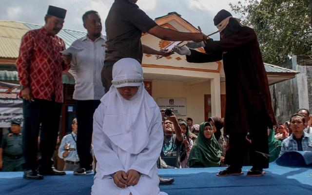 Azotan con vara a pareja por besarse en público en Indonesia - Joven siendo azotada. Foto de Barcroft Images