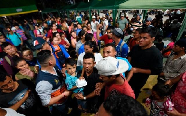 Caravana migrante rompe portón en frontera y cruza hacia México - Foto de AFP