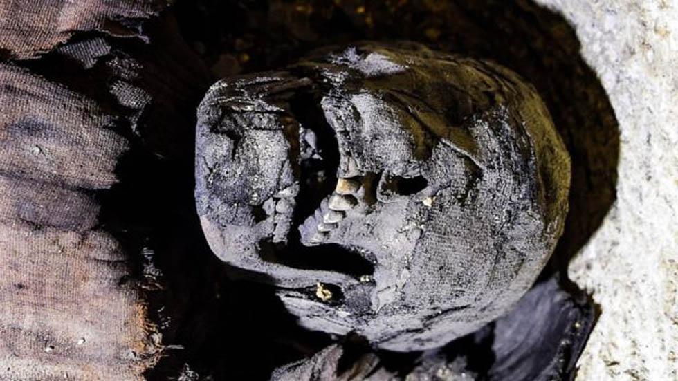 Cráneo parcialmente cubierto de lino. Foto de AFP