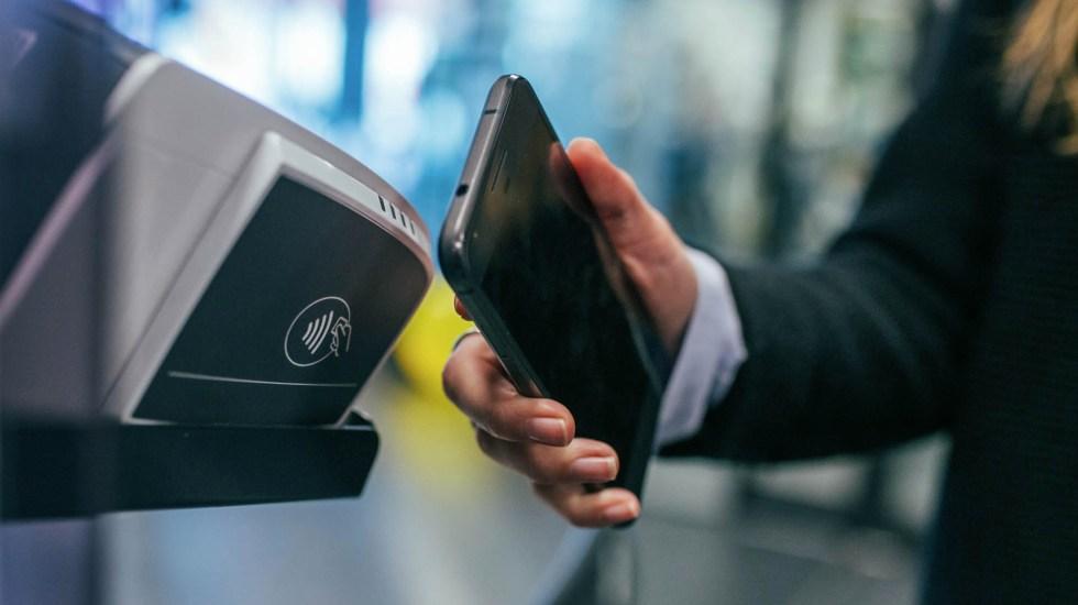 Banxico y Amazon trabajan en método de pago por código QR - Fotografía ilustrativa de una persona pagando con su celular. Foto de Jonas Leupe para Unsplash