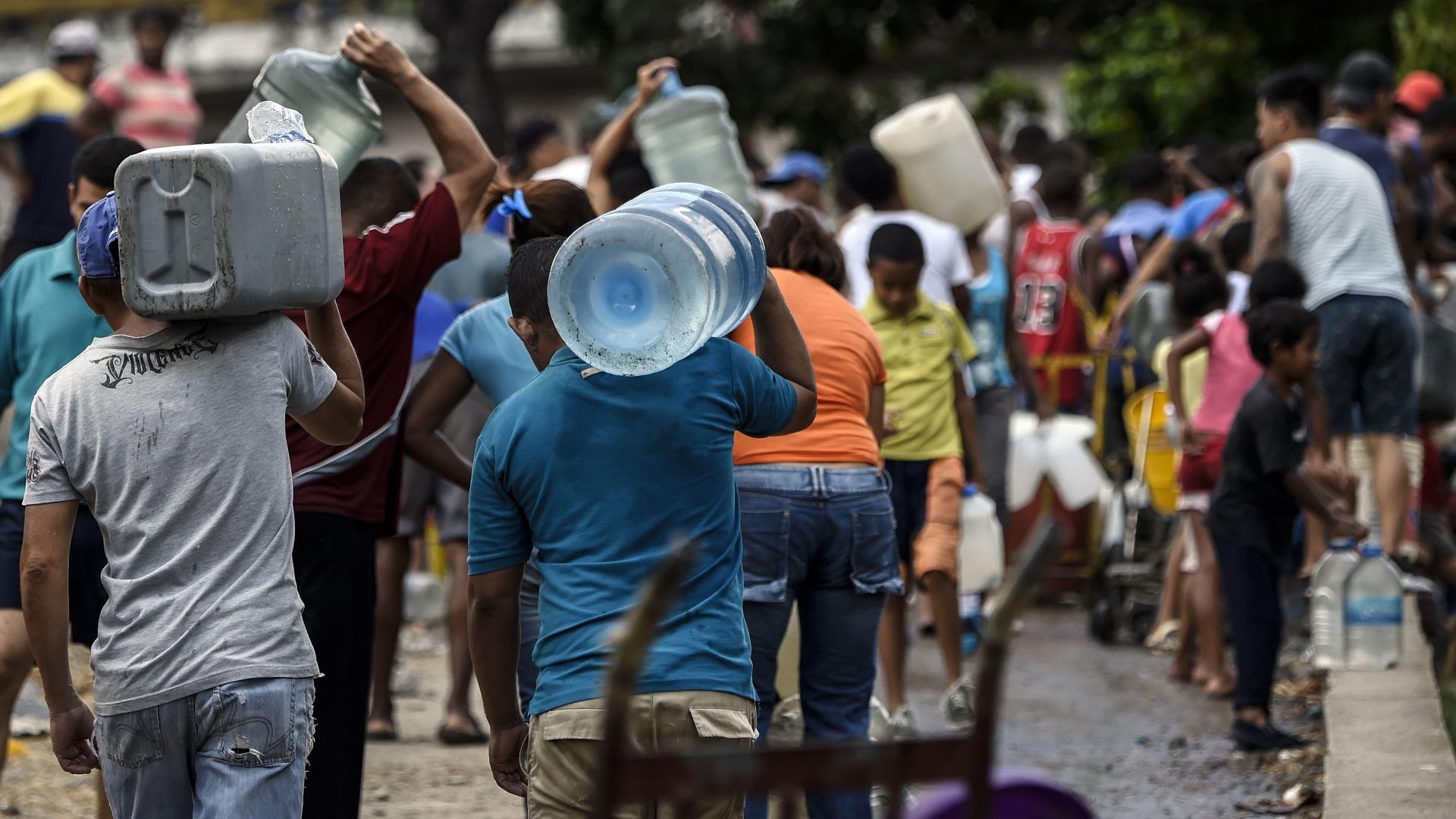 Gente acarreand agua por falta del servicio por apagón. Foto de AFP / Juan Barreto