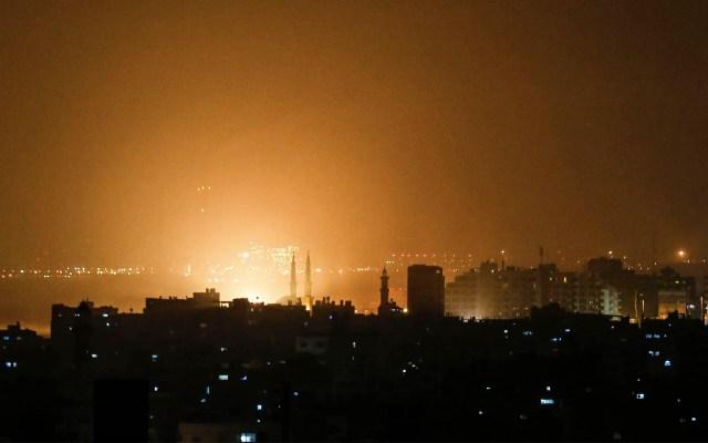 Israel ataca posiciones en Gaza en respuesta a lanzamiento de cohetes - El cielo sobre los edificios en la Franja de Gaza se ilumina de color naranja durante un ataque aéreo israelí en la ciudad de Gaza el 14 de marzo de 2019. Foto de Mahmud Hams/AFP