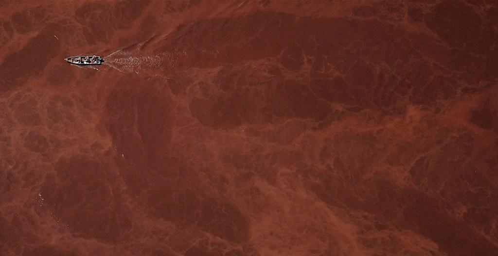 Alto riesgo de ruptura de dique minero en Brasil - Un bote navega por el río Paraopeba, en Juatuba, estado de Minas Gerais, Brasil, el 18 de marzo de 2019, donde se instaló una membrana de retención para tratar de retener el lodo, luego del colapso de una represa en una mina de mineral de hierro perteneciente a Brasil. Foto de Douglas Magno/AFP
