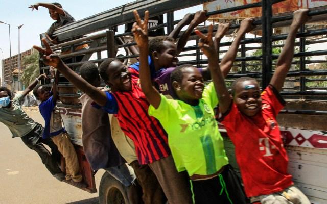 Jóvenes sudaneses señalando la victoria en mitin en Jartum, Sudán - Jóvenes sudaneses muestran signos de victoria mientras viajan en una camioneta durante un mitin fuera del complejo del ejército en la capital de Sudán, Jartum. Foto de Ebrahim Hamid / AFP.