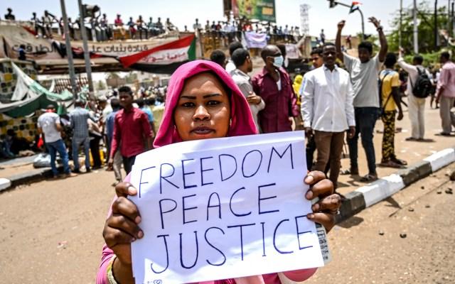 Siguen las protestas en Sudán - Manifestante sudanés sostiene cartel durante protesta frente al complejo del ejército en la capital, Jartum. Se espera que las multitudes converjan el jueves en la capital sudanesa mientras los manifestantes celebran una semana desde que el ejército derrocó al presidente Omar al-Bashir, decidido a completar su revolución en busca de un gobierno civil. Foto de OZAN KOSE / AFP.