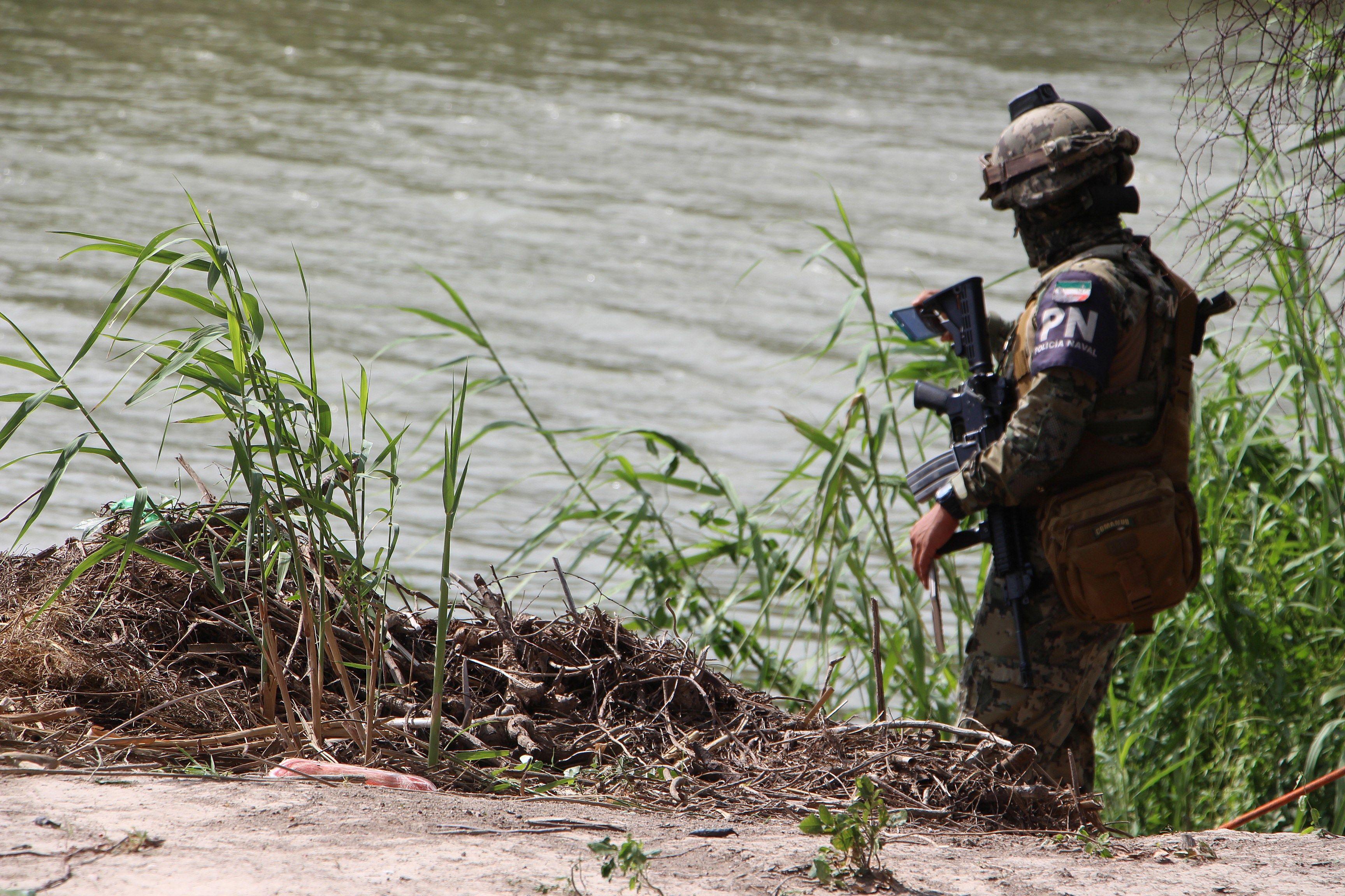 Miembro de la Policía mexicana patrulla la zona donde fueron hallados los cuerpos sin vida de un presunto migrante y su bebé a una orilla del Río Bravo en Matamoros, frontera con EE.UU., en Tamaulipas. Foto de EFE/ Abraham Pineda-Jácome.