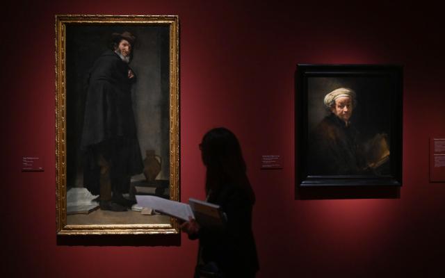 """Velázquez, Rembrandt y Vermeer ponen en común su legado - GRAF2145. MADRID, 21/06/2019.- Una mujer observa dos obras que forman parte de la exposición """"Velázquez, Rembrandt, Vermeer. Miradas afines"""", un ambicioso proyecto que, con la colaboración especial del Rijksmuseum de Ámsterdam, se dedica a la pintura holandesa y española de finales del siglo XVI y del siglo XVII, en el Museo del Prado. EFE/Fernando Villar"""