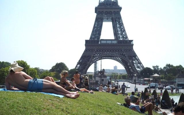 París supera récord de calor con 41 grados - Gente tomando el sol en las inmediaciones de la Torre Eiffel. Foto de EFE