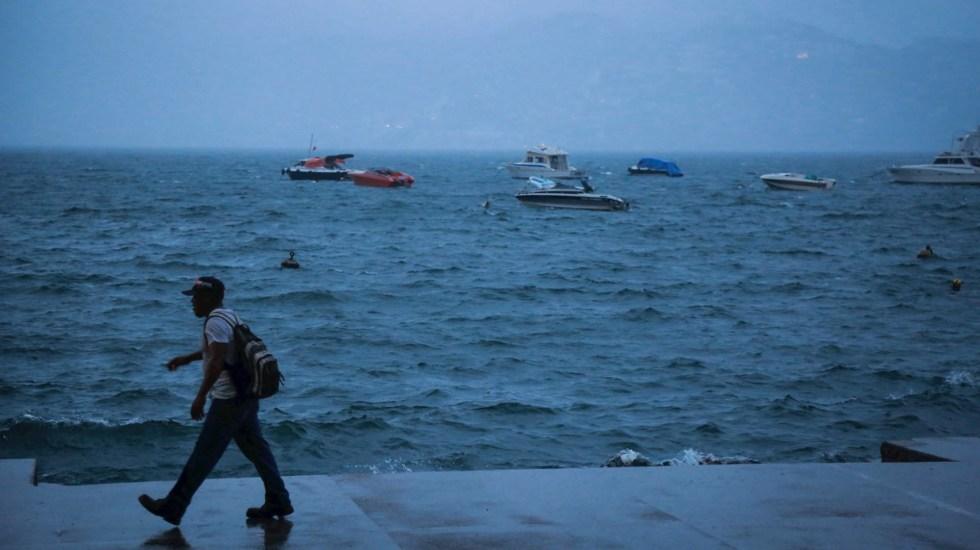Tormenta tropical Mario se une a Lorena en el Pacífico mexicano - Un hombre camina este martes junto al mar en el balneario de Acapulco, en el estado de Guerrero (México). Foto de EFE/David Guzmán