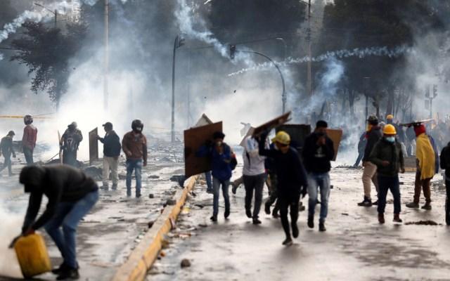 Quito amanece devastada por protestas contra ajustes económicos - Manifestantes corren entre los gases lacrimógenos lanzados por la policía en una nueva jornada de choques este domingo, en Quito. Foto de EFE