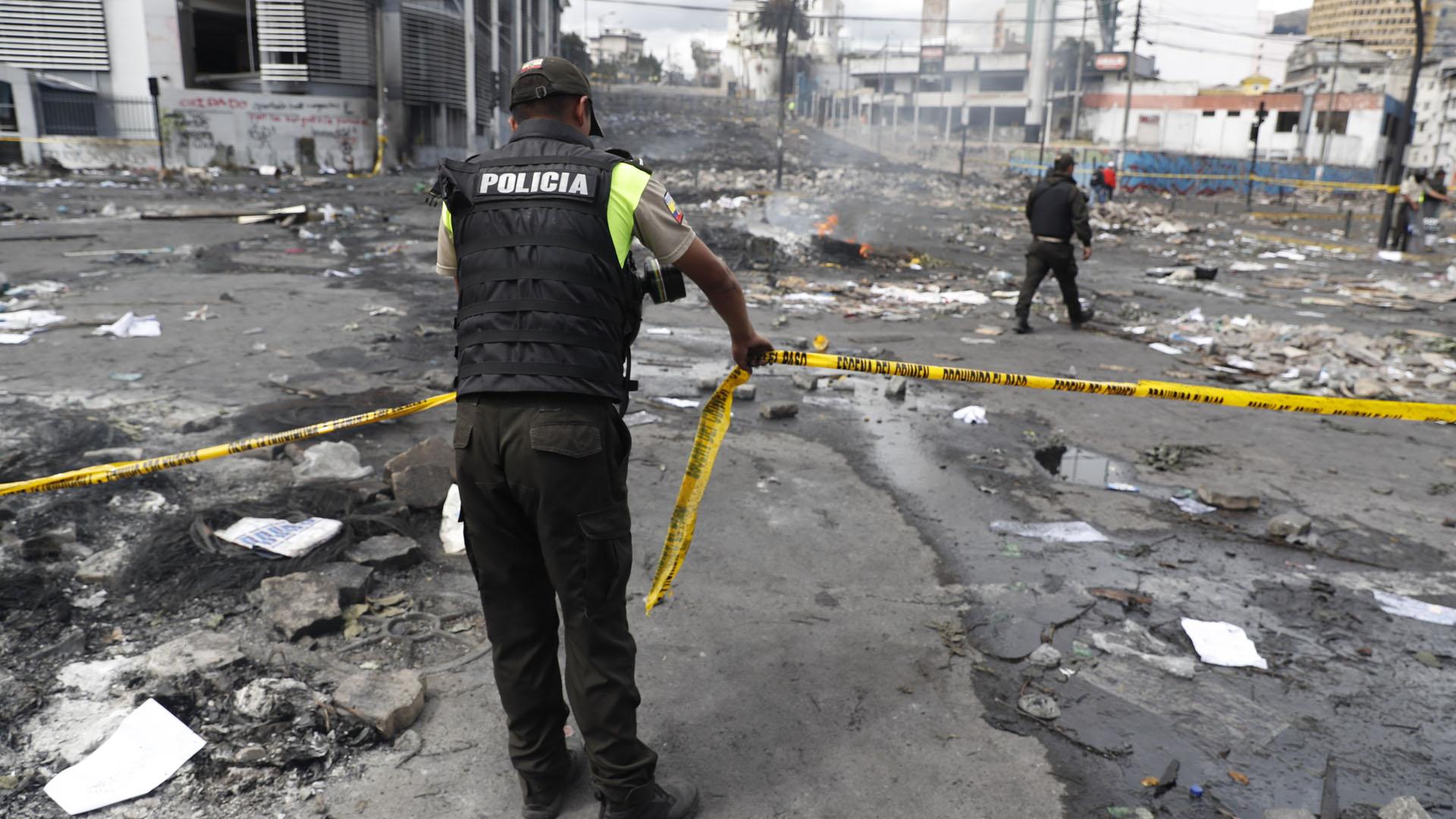 Policías acordonan este domingo las calles aledañas a la sede de la Contraloría, que fue tomada y atacada el sábado por manifestantes. Foto de EFE