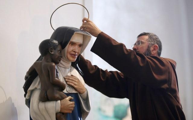Papa Francisco canoniza por primera vez a una mujer brasileña - Un sacerdote coloca una aureola sobre una escultura con la imagen de la Irma Dulce, en una iglesia de Brasil. Foto de EFE