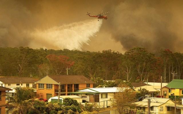 Incendios en Australia dejan un muerto y 100 casas destruidas - Un helicóptero del Servicio Rural de Bomberos descarga agua sobre los incendios que arrasan este viernes los bosques de la ciudad de Harrington (Australia). Foto de EFE/Shane Chalker