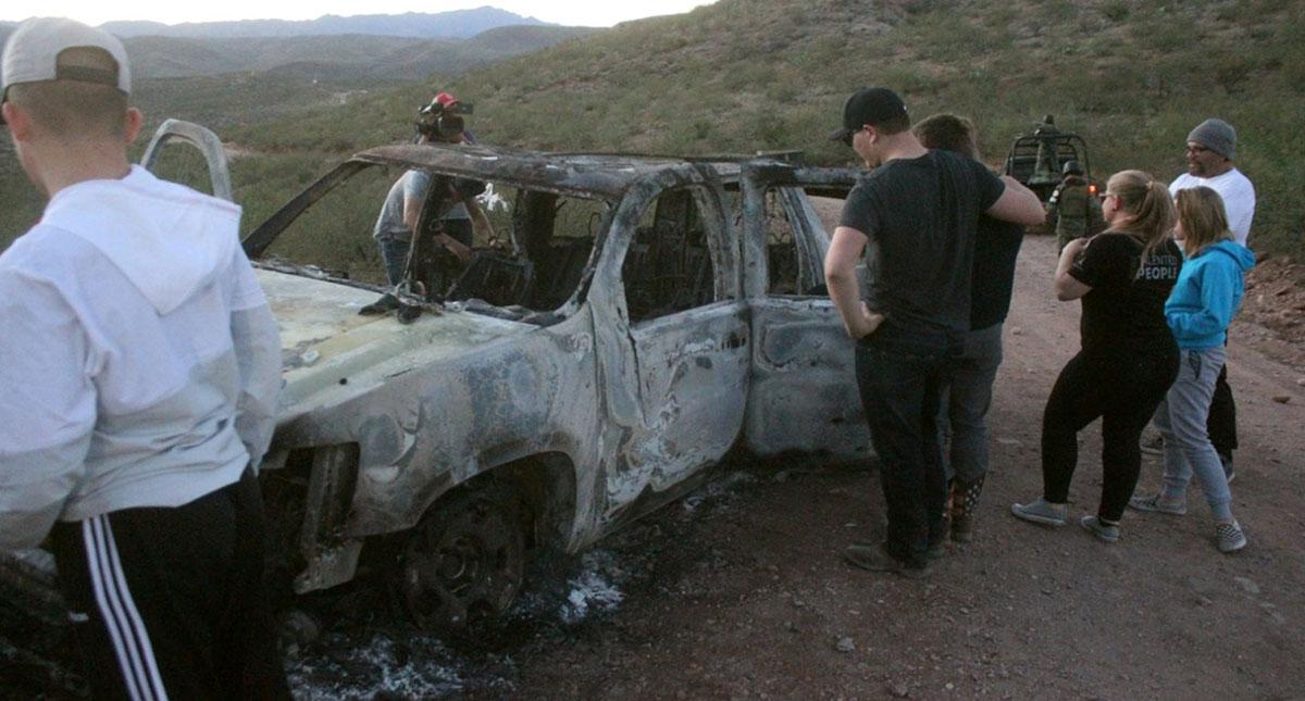 Miembros de la familia LeBarón observan este miércoles un vehículo calcinado donde fueron ultimados sus familiares. Foto de EFE