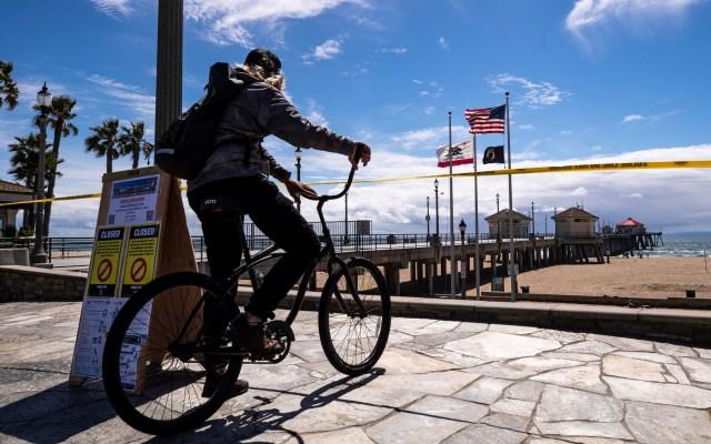 López-Gatell pide a paisanos en EE.UU. evitar venir a México por COVID-19 - Ciclista estadounidense frente a playa cerrada por COVID-19. Foto de EFE
