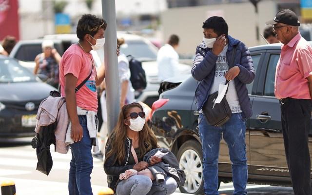 Asciende a 18 el número de víctimas por COVID-19 en Perú - Un grupo de personas utiliza tapabocas como medida de protección en Lima. Foto de EFE