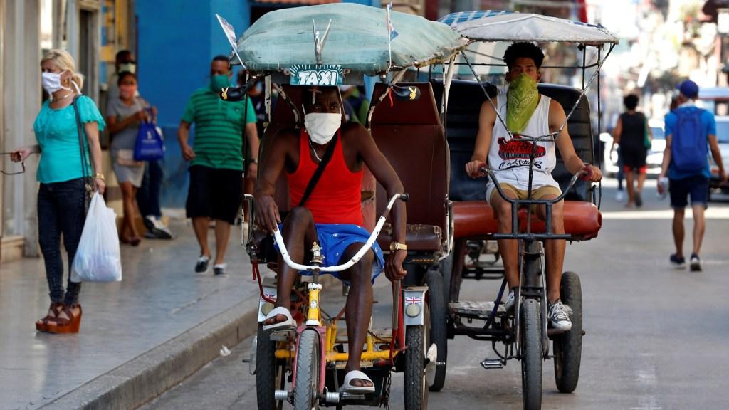 Cuba acumula 669 casos de COVID-19 y 18 muertes - Conductores de bicitaxis con mascarillas pasan por una calle en La Habana. Foto de EFE
