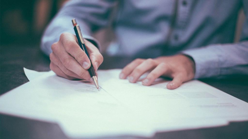UIF congela cuentas de 42 empresas por operaciones simuladas - Imagen ilustrativa de una persona firmando un documento. Foto de Unsplash