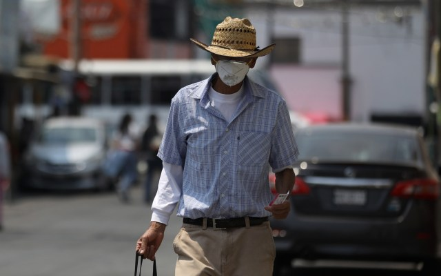 Estado de México pasa a Semáforo Naranja de riesgo por COVID-19 - Hombre camina en calles de Ecatepec tras realizar compras. Foto de EFE