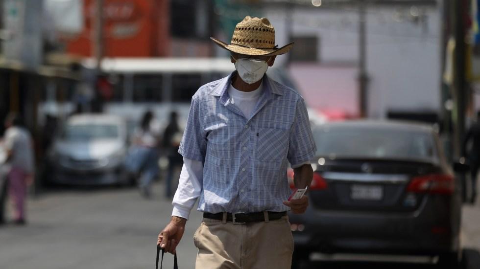 Ecatepec, donde la cuarentena no es opción - Hombre camina en calles de Ecatepec tras realizar compras. Foto de EFE