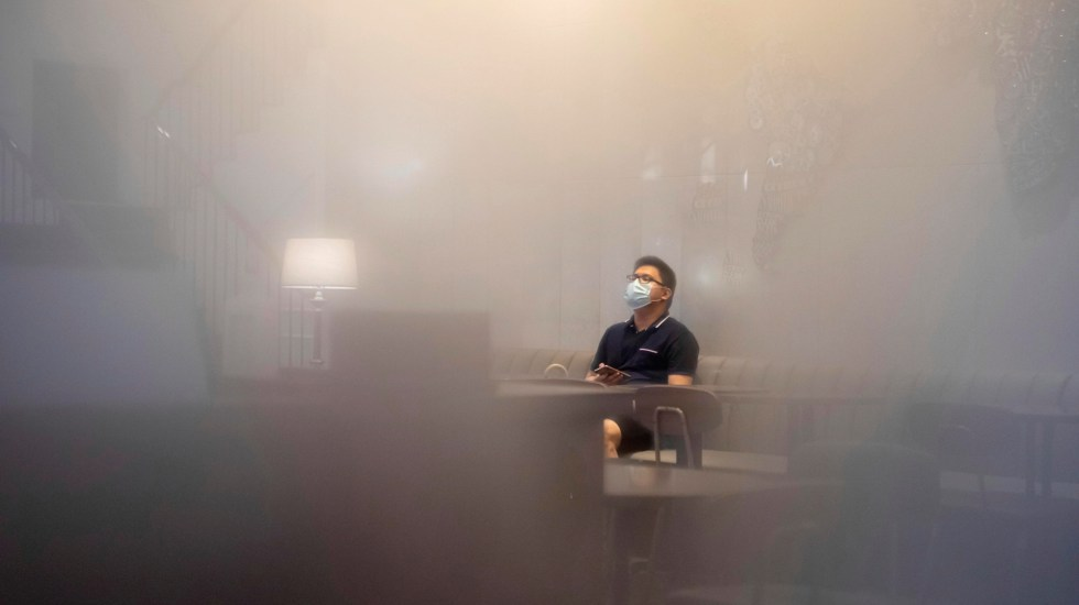 COVID-19 rompe récord de nuevos contagios en el mundo, con 115 mil casos positivos en 24 horas - Hombre al interior de cafetería en China, visto desde una ventana empañada por la humedad en el ambiente. Foto de EFE