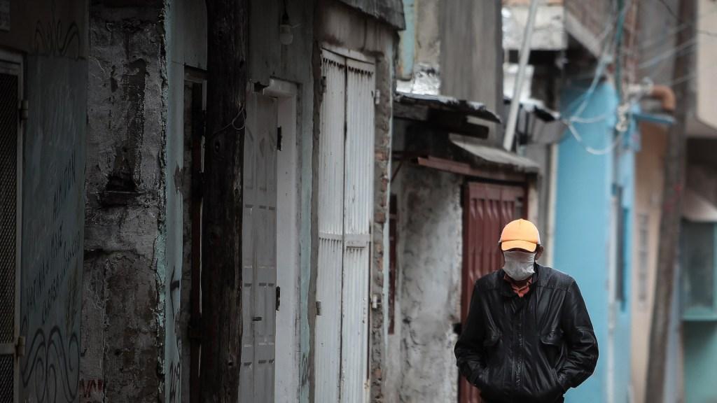 COVID-19 dejará 29 millones de nuevos pobres en Latinoamérica, revela ONG - Hombre con cubrebocas camina por calles de Villa 21-24, el barrio más pobre de Argentina. Foto de EFE