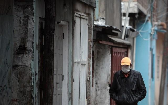 Cepal propone ingreso básico para personas en pobreza por COVID-19 - Hombre con cubrebocas camina por calles de Villa 21-24, el barrio más pobre de Argentina. Foto de EFE