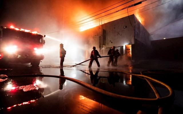 Manifestaciones en Los Ángeles por la muerte de George Floyd - Bomberos tratan de extinguir las llamas en una tienda que fue saqueada e incendiada durante las manifestaciones por quinto día consecutivo por la muerte de George Floyd, en Los Ángeles, Estados Unidos. Foto de EFE/ Etienne Laurent.