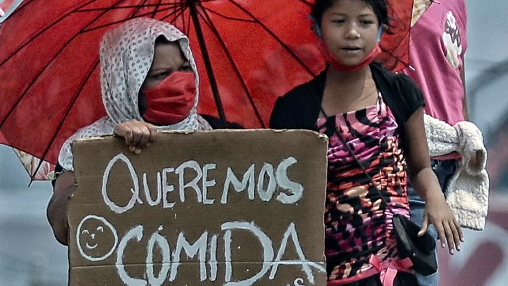 Pandemia extiende la pobreza a 118 millones de mujeres en Latinoamérica - Una madre con sus hijas pide ayuda ante COVID-19 en calles de la ciudad de Tegucigalpa, Honduras. Foto de EFE