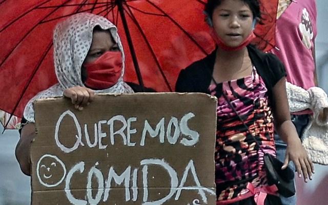 Pandemia provocará dura recesión global y millones de nuevos pobres, prevé ONU - Una madre con sus hijas pide ayuda ante COVID-19 en calles de la ciudad de Tegucigalpa, Honduras. Foto de EFE