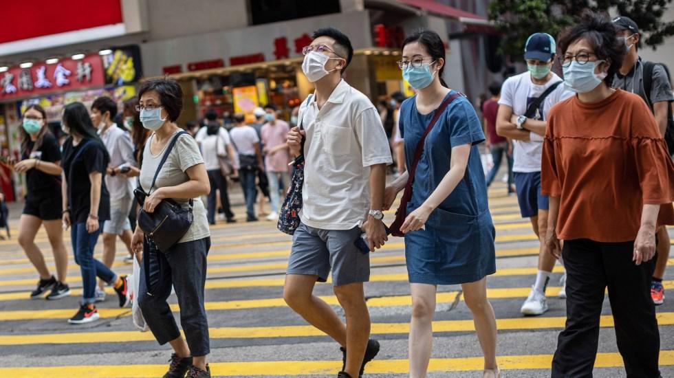 China no registra infectados de COVID-19 en un día por primera vez - Varios peatones cruzan en la intersección de una calle comercial en Hong Kong, China. Foto de EFE
