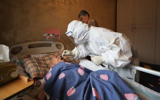 COVID-19 es el enemigo común de la humanidad, asegura investigadora china - Prueba de coronavirus a adulto mayor en Wuhan, China. Foto de EFE