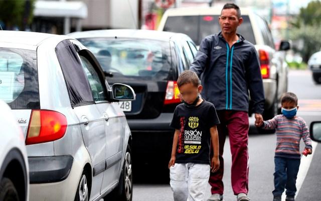 Pobreza infantil en América Latina crecerá a 46 % a finales de año por COVID-19 - Un ciudadano venezolano y sus dos hijos piden dinero en Quito, Ecuador