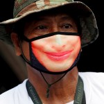 Manila extiende la cuarentena hasta fin de año y suma nueve meses y medio - Un funcionario lleva una mascarilla con una sonrisa impresa mientras reparte material sanitario y otros productos a la población en la Ciudad de Paranaque, al sur de Manila, Filipinas. Foto de EFE/Francis R. Malasig.