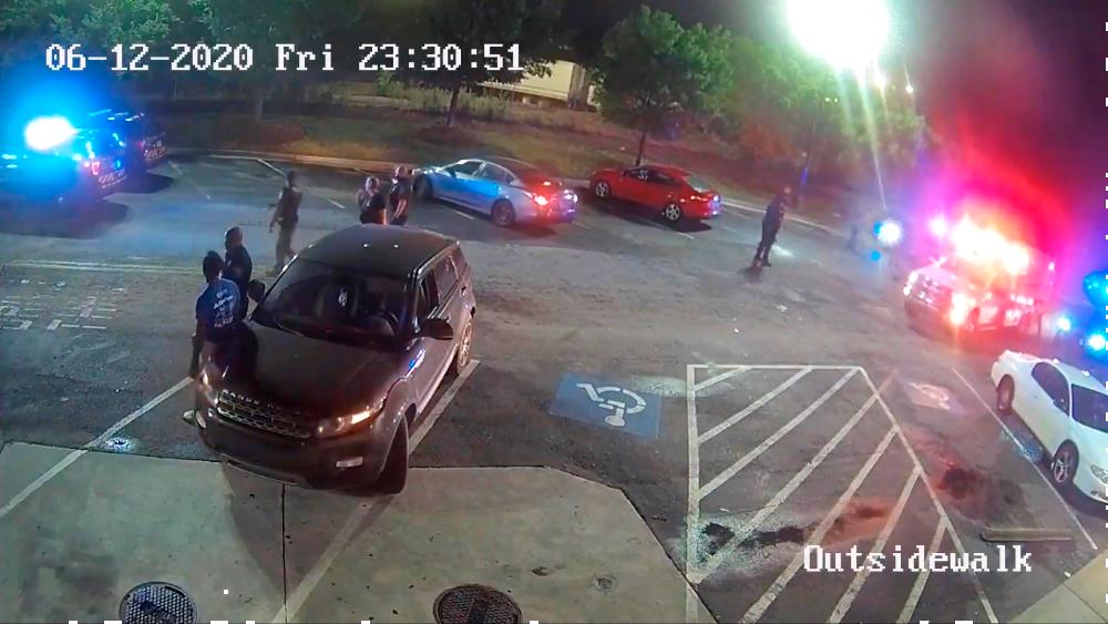 Trump anuncia decreto para incentivar buenas prácticas de la policía - Captura de un video de vigilancia publicado por la Oficina de Investigación de Georgia (GBI) que muestra una ambulancia (R) llegando a auxiliar a Rayshard Brooks después de que un oficial de policía de Atlanta le disparó y lo mató el 12 de junio en Atlanta, Georgia, el 14 de junio de 2020. Foto de EFE