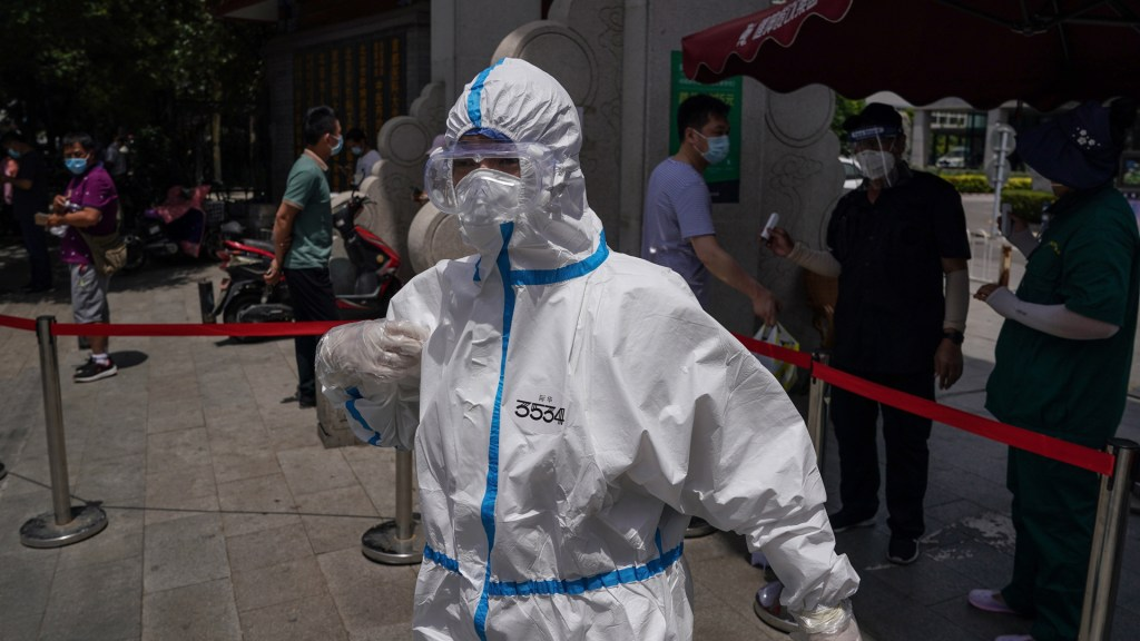 Beijing reporta 21 nuevos casos de COVID-19 tras brote - Trabajador sanitario en China que aplica pruebas de coronavirus en inmediaciones de un hospital. Foto de EFE