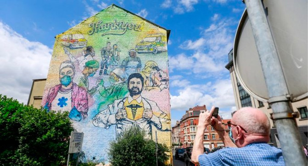 Artistas callejeros pintan mural en Bruselas para honrar a quienes luchan contra el COVID-19 - Bruselas, muro intervenido por artistas callejeros
