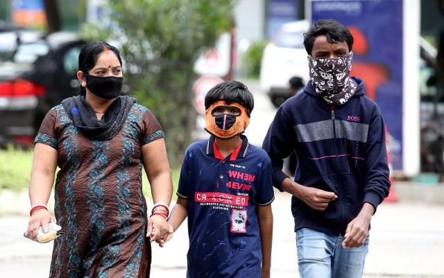 El mundo suma 11 millones de casos y 527 mil decesos por COVID-19 - Familia con cubrebocas para prevenir el coronavirus en calles de India. Foto de EFE
