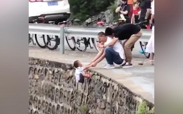 #Video Hombre sujeta a niño sobre un acantilado solo para tomarle una foto - Hombre sujeta a un niño sobre un acantilado