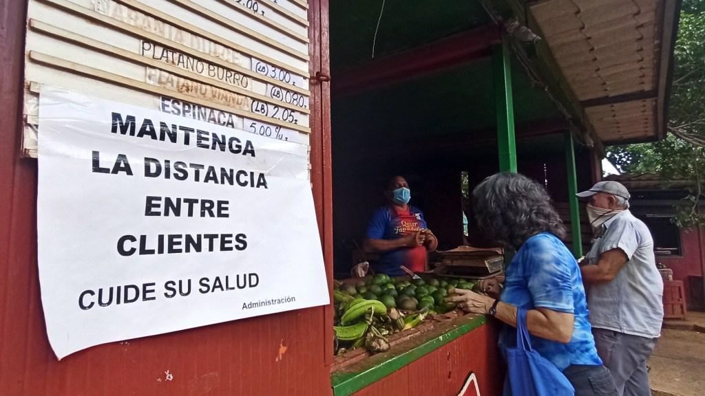 """""""Será una gran ola"""", OMS descarta segunda o tercera ola de COVID-19 - Llamado a clientes de verdulería en Cuba a mantener la sana distancia. Foto de EFE"""