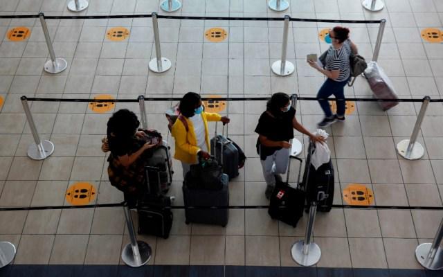 Países restringen los viajes para evitar riesgos, afirma OMS - Viajeros hacen fila para realizar su registro de ingreso en el Aeropuerto Internacional de Tocumen, en Ciudad de Panamá, Panamá. Foto de EFE