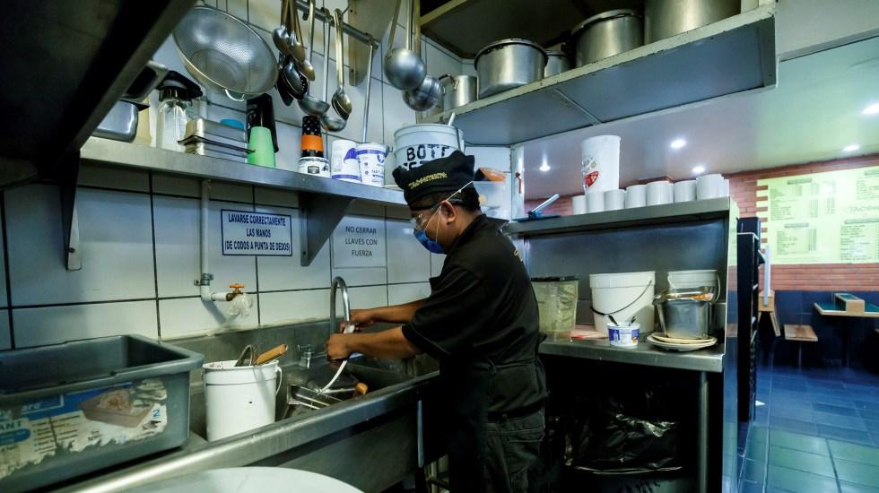 Banxico advierte impactos regionales diferenciados por crisis de COVID-19 - Empleado de restaurante en la CDMX. Foto de EFE
